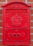 Boîte aux lettres rouge en métal sur le mur de briques Image libre de droits