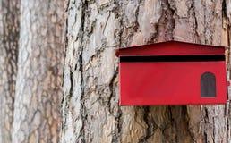 Boîte aux lettres rouge sur le fond d'arbre Photographie stock libre de droits