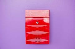 Boîte aux lettres rouge sur le fond violet Photo stock