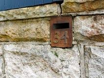 Boîte aux lettres rouillée en métal, numéro 34 Photographie stock libre de droits