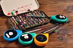 Boîte avec des amorces et des cannes à pêche pour la pêche d'hiver sur un OE brun Image stock