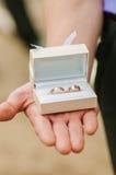 Boîte avec des anneaux de mariage dans des mains Image stock