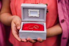 Boîte avec des anneaux de mariage dans les mains de la fille pour la cérémonie de fiançailles Images libres de droits