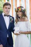 Boîte avec des anneaux de mariage dans des mains de marié et de jeune mariée Image stock