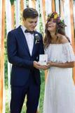 Boîte avec des anneaux de mariage dans des mains de marié et de jeune mariée Images stock