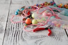 Boîte avec des coeurs de perles, de pinces et en verre pour créer le bijou fabriqué à la main Image libre de droits