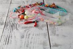 Boîte avec des coeurs de perles, de pinces et en verre pour créer le bijou fabriqué à la main Photo libre de droits
