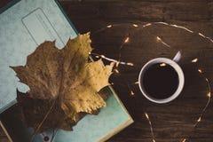 Boîte avec des feuilles sur une table et un café Image stock