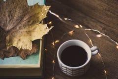 Boîte avec des feuilles sur une table et un café Photo libre de droits