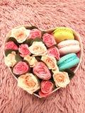 Boîte avec des roses et des biscuits de macaronis Photo stock