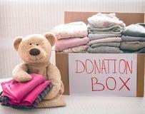 Boîte avec des vêtements pour la charité photo stock