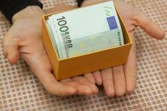 Boîte avec l'euro dans les mains Image libre de droits