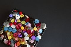 Bo?te avec les boutons multicolores sur le fond noir photographie stock