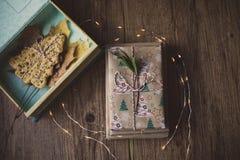 Boîte avec les feuilles et le biscuit de Noël sur une table avec des lumières de Noël Photos libres de droits