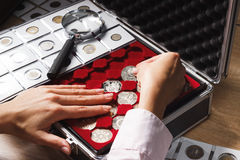 Boîte avec les pièces de monnaie et la loupe collectables Image libre de droits