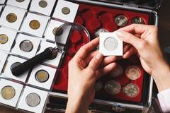Boîte avec les pièces de monnaie et la loupe collectables Images stock