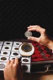 Boîte avec les pièces de monnaie et la loupe collectables Photos stock