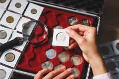 Boîte avec les pièces de monnaie et la loupe collectables Photos libres de droits