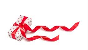 Boîte avec un cadeau avec l'image des coeurs attachés avec un isolat de ruban sur un fond blanc Concept de célébration de jour du photographie stock