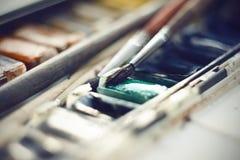 Boîte avec une vieille palette et des brosses d'aquarelle de cru images libres de droits