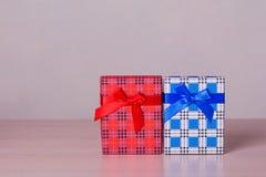 Boîte-cadeau à carreaux rouges et bleus sur la table en bois Images stock