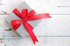 Boîte-cadeau argenté avec l'arc rouge de ruban sur le fond de vintage Photographie stock