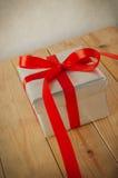 Boîte-cadeau argenté avec traîner le ruban rouge Photographie stock libre de droits