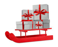 Boîte-cadeau argentés rouges de Noël sur le traîneau en bois rouge du père noël Photos libres de droits