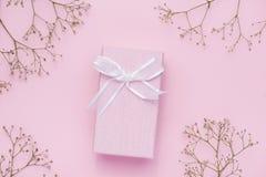 Boîte-cadeau attaché avec le ruban rose et les fleurs blanches pour le jour de mères Photos libres de droits