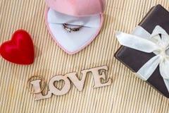 Boîte-cadeau avec amour en bois des textes d'anneau d'or Photos stock