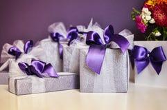 Boîte-cadeau avec des arcs de pourpre sur la table blanche Images libres de droits