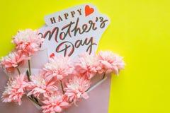 Boîte-cadeau avec des fleurs et carte de voeux pour le jour du ` s de mère sur le fond jaune lisianthus, fleurs de chrysanthème h Photo stock