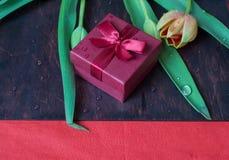 Boîte-cadeau avec des tulipes sur le mur en bois Images libres de droits