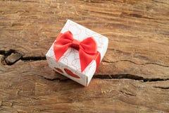 Boîte-cadeau avec deux coeurs rouges de côté sur le fond en bois Photographie stock
