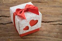 Boîte-cadeau avec deux coeurs rouges de côté sur le fond en bois Images libres de droits
