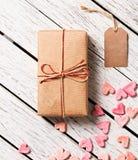 Boîte-cadeau avec l'étiquette de cadeau et le tas vides des coeurs Image libre de droits