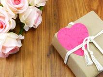 Boîte-cadeau avec l'étiquette rose de papier de coeur et la fleur artificielle de rose Photographie stock