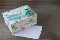 Boîte-cadeau avec l'étiquette vide sur le fond en bois Photos libres de droits