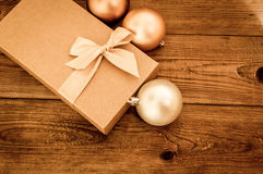 Boîte-cadeau avec l'arc d'or avec des boules de hristmas sur le fond en bois photographie stock libre de droits