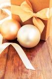 Boîte-cadeau avec l'arc d'or avec des boules de hristmas sur le fond en bois image libre de droits