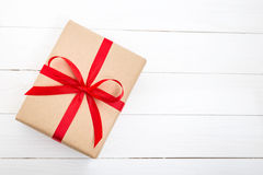 Boîte-cadeau avec l'arc rouge de ruban sur le fond en bois blanc Photos stock