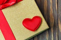 Boîte-cadeau avec l'arc rouge et coeur sur le fond en bois Cadeau avec amour Photo stock