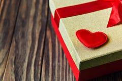 Boîte-cadeau avec l'arc rouge et coeur sur le fond en bois Cadeau avec amour Image libre de droits