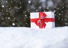 Boîte-cadeau avec l'arc rouge sur la neige dans l'objet de la forêt une d'hiver Concept de vacances de Noël Images libres de droits