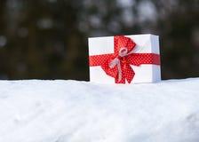 Boîte-cadeau avec l'arc rouge sur la neige dans l'objet de la forêt une d'hiver Concept de vacances de Noël Photographie stock