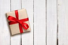 Boîte-cadeau avec l'arc rouge sur le bois blanc Images stock