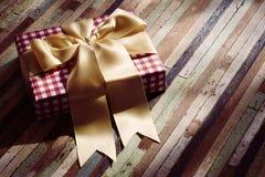 Boîte-cadeau avec l'arc sur le ton en bois de vintage de fond La vie toujours de Image libre de droits