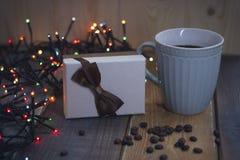Boîte-cadeau avec l'arc, tasse bleue, lumières, sur le tablenn de Noël Photographie stock libre de droits
