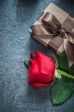 Boîte-cadeau avec la rose brune de rouge d'arc sur la célébration noire de fond Photos libres de droits