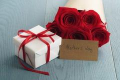Boîte-cadeau avec le bouquet de roses rouges et carte de papier de jour de mères sur la table en bois bleue Photo libre de droits